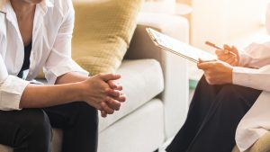 A counselor with a clipboard gestures with their hand as they sit across from their client. This could represent what counseling in Santa Fe, NM might look like. Contact a Santa Fe therapist for the support you deserve.