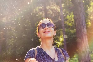 A woman wearing sunglasses smiles as the sunlight shines down through the trees. Her bright smile could represent the joy of overcoming trauma after meeting with a Santa Fe therapist. Contact us for counseling in Santa Fe, NM. Our Santa Fe therapy services are here for you.